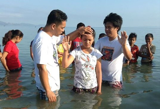 Bro. Robby Landicho and Bro. Michael Mayorca baptize a participant of the youth camp in Masbate.